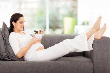 Healthy pregnant woman eating vegetable salad