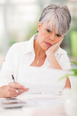 stressed senior woman paying her bills