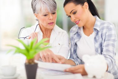 young woman helping her mother paying bills