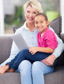 Fotografie little girl sitting on grandmothers lap with notebook computer