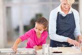 grandmother baking cookies with granddaughter