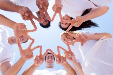 group of people hands forming a star shape