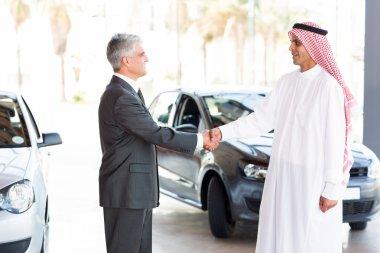 Car dealer handshake with arabian man