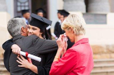 Female graduate hugging her father