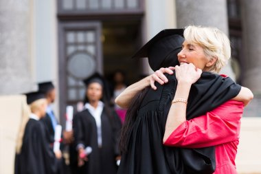 Graduate hugging mother