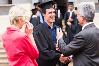 Graduate handshaking with his grandfather