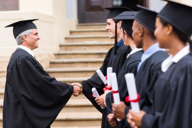 Graduates in line handshaking with dean