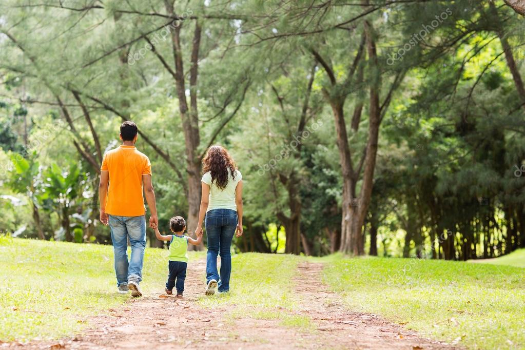 family holding hands walking in forest