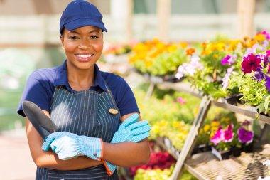 black nursery worker in greenhouse