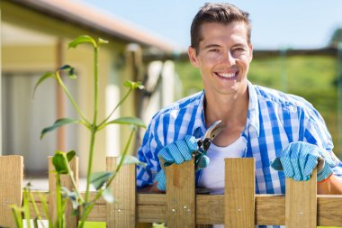 Man standing by garden fence