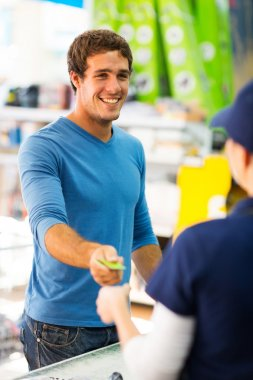 Man handing over card to cashier