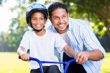 Man helping son ride bike