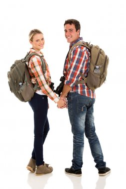 Couple with backpacks looking back