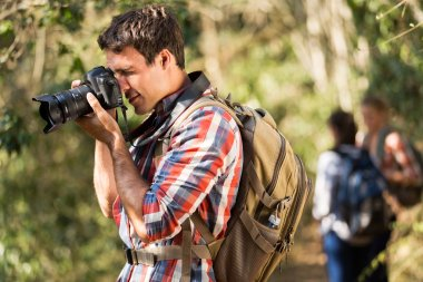 young man taking photos during hiking