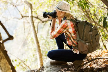 young woman taking photos in forest