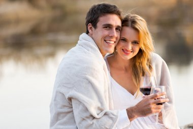 Couple wrapped in blanket holding glasses of wine