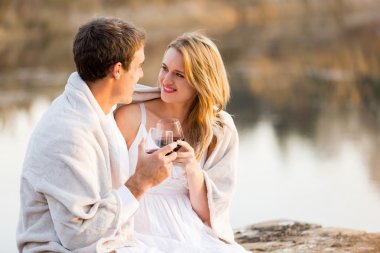 Young couple sitting by a lake with wine