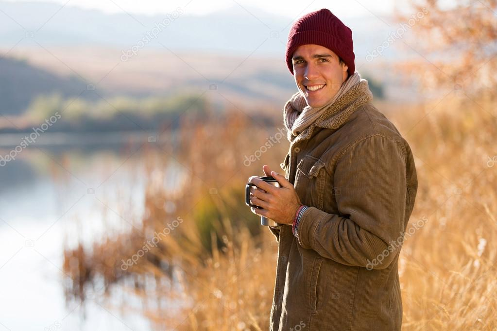 man drinking coffee outdoors in fall
