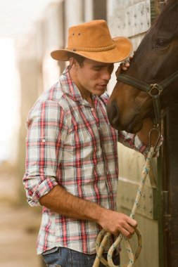 cowboy whispering to a horse