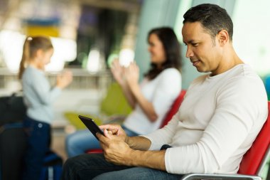 Man at airport using tablet