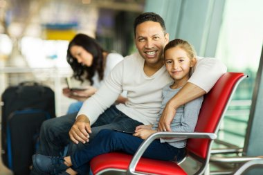 Portrait of lovely father and daughter sitting on airport bench with tablet pc waiting for flight stock vector