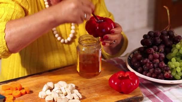 žena připravuje nakládané papriky plněné vinné hrozny