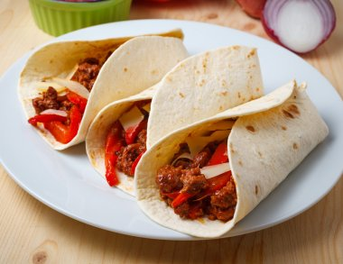 Tortillas filled with with beef meat, pepperoni, onions, cheese and tomato sauce stock vector