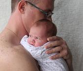 Otec drží novorozeně