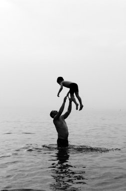 father and son swimming in the sea at sunset