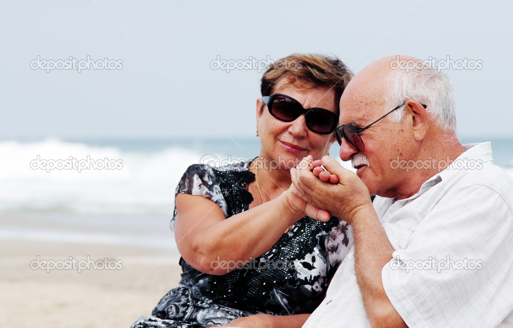 Portrait of happy senior couple sitting together on a beach