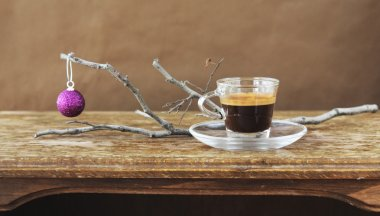 cup of coffee on vintage table with christmas ball