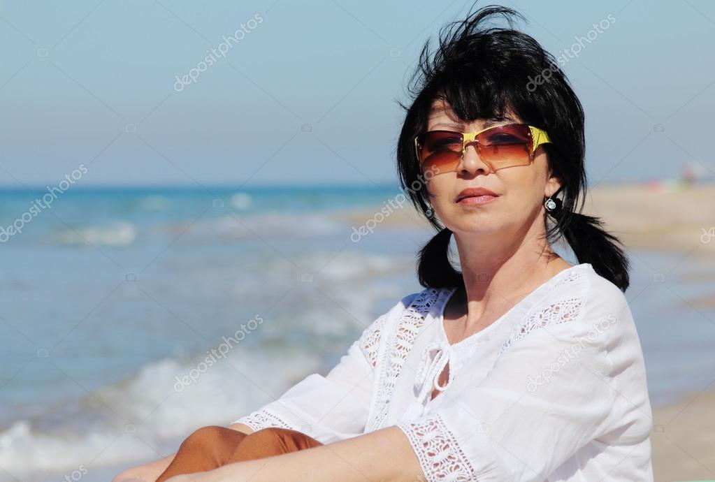 Woman sits on the beach