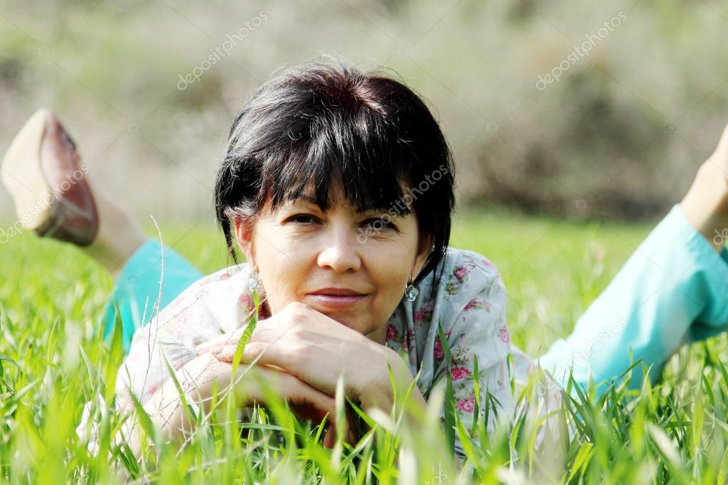 Mature woman lying in grass