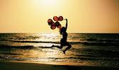 Krásná žena s barevnými balónky mimo