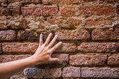 ruka se dotýká stěny