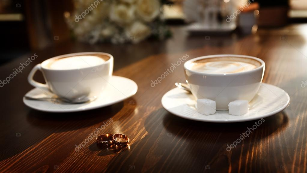 Two Cups Of Coffee On The Table With Wedding Rings Stock Photo