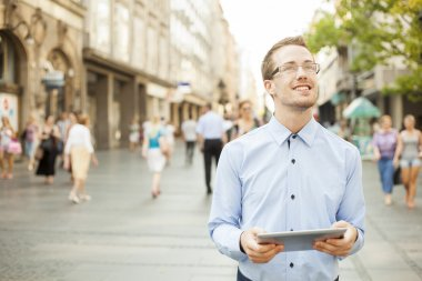 Man on street looking up, hold tablet computer in hands
