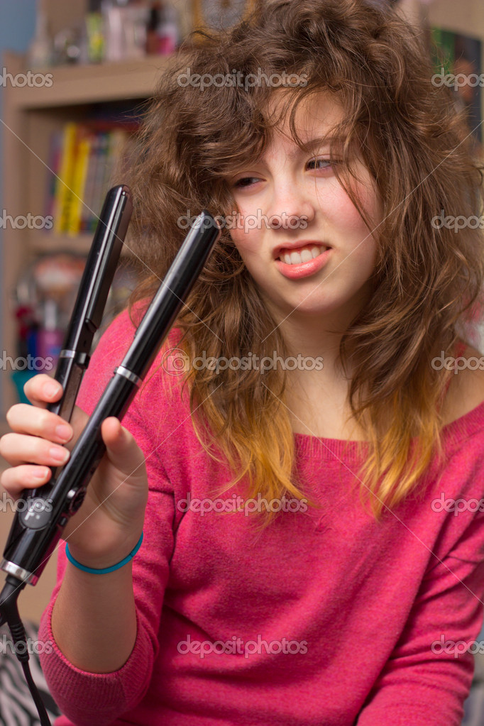 Cute teenage girl with messy hair and flatiron straightener — Photo by ...