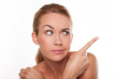 Sceptical woman pointing with her finger