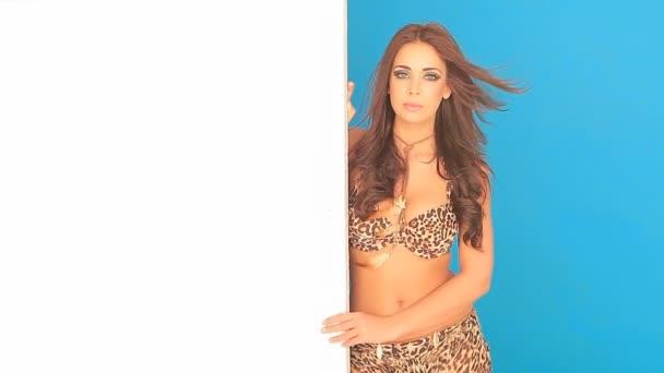 mladá žena v plavkách drží prázdné cedulky