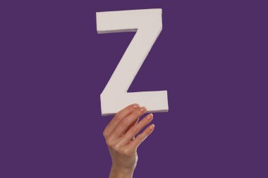 Female hand holding up the letter Z from the bottom
