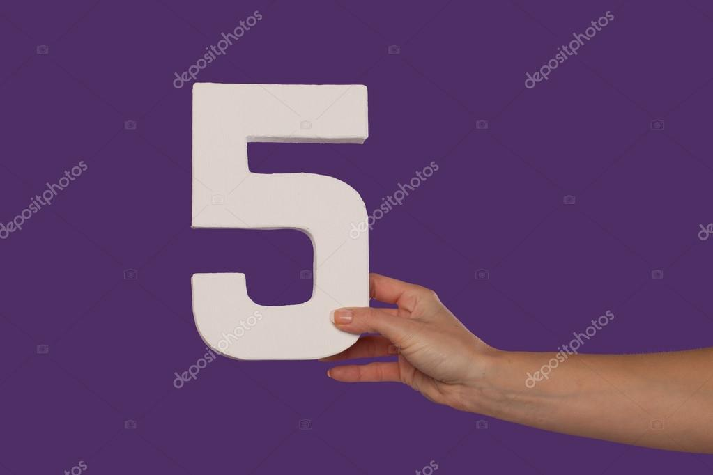 Female hand holding up the number 5 from the right
