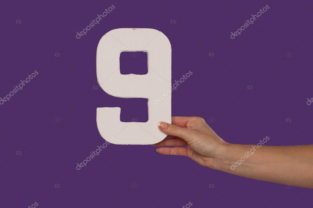 Female hand holding up the number 9 from the right