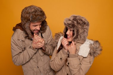 Happy couple in warm winter clothing wearing warm furry caps and jackets laughing as they stand looking at each other rubbing their hands against the cold, on an orange studio background stock vector