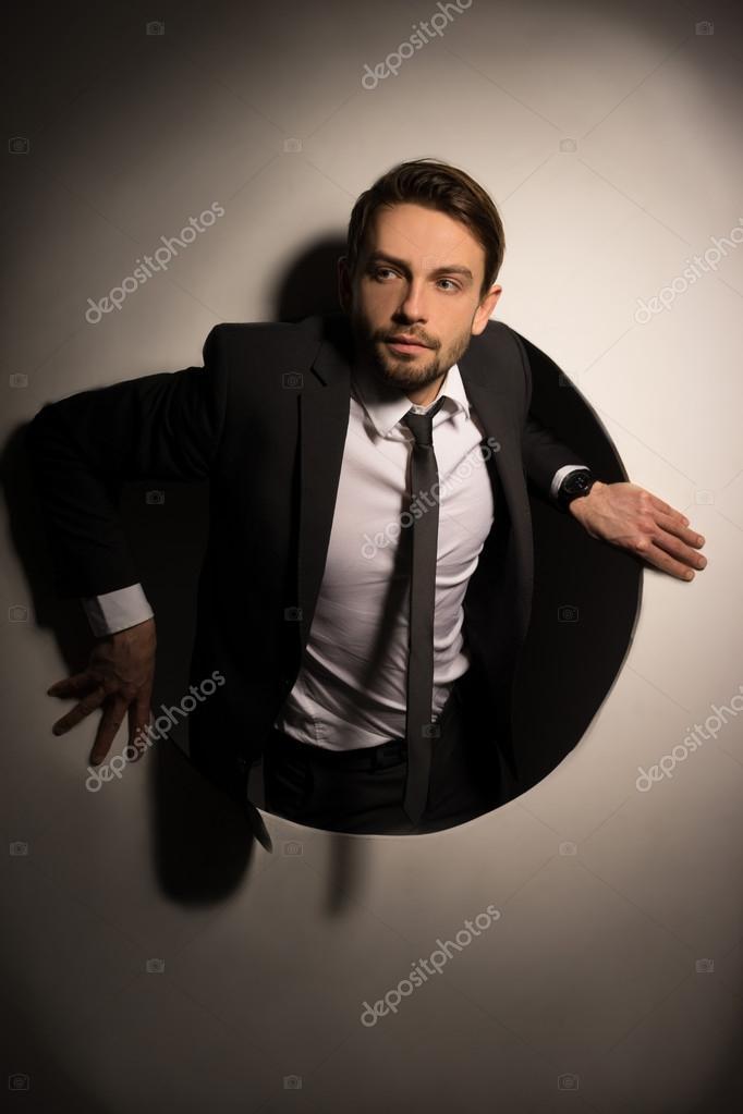 Businessman Climbing Out Of A Circular Hole Stock Image