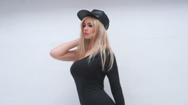 sexy žena nosí černou koženou čepici a šaty na bílém pozadí