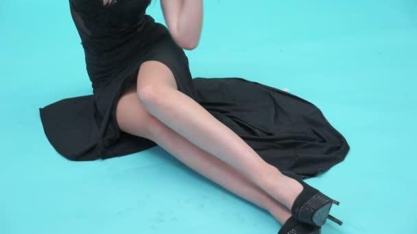 szexi nő visel hosszú fekete ruhában ült a padlón a stúdióban