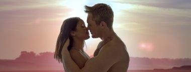 Couple enjoying a romantic sunset kiss