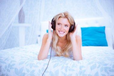 Quiet woman enjoying some music in her bedroom