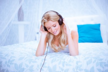 Quiet woman enjoying some music in her bedroom